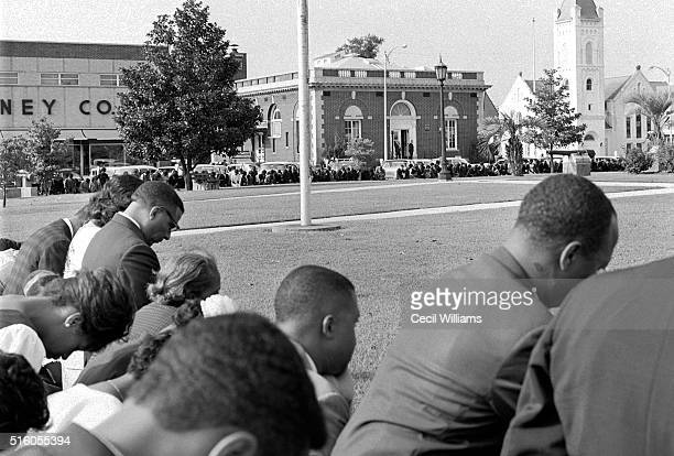 In Memorial Plaza demonstrators kneel and pray during an antisegregation rally Orangeburg South Carolina 1963 The building at rear center is the old...
