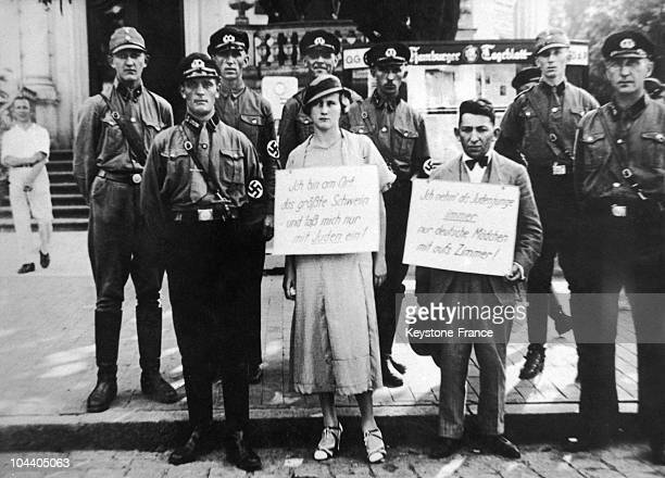 In misunderstood national and racial pride these Hamburg SA and SS members had themselves photographed with these two young people who were driven...
