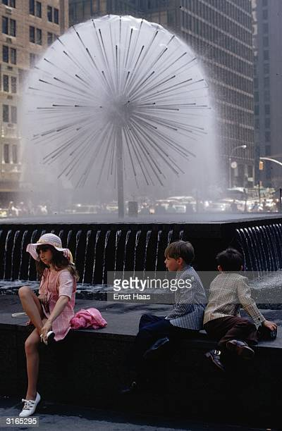 In New York children sit by a fountain that looks like a large dandelion 'clock'