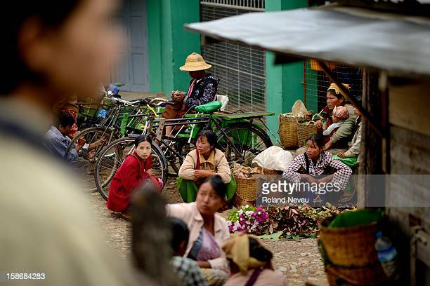 In Nyaug Shwe several women form oulyings villages are crouching on the street near the town's market and selling their farm products