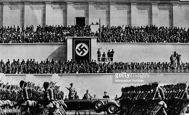 In occasion of the Congress of the Nazi Party Fuhrer and Chancellor of Germany Adolf Hitler on an open car watching a military parade inside Zeppelin...