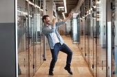 In office hallway dancing worker got promotion celebrating business success