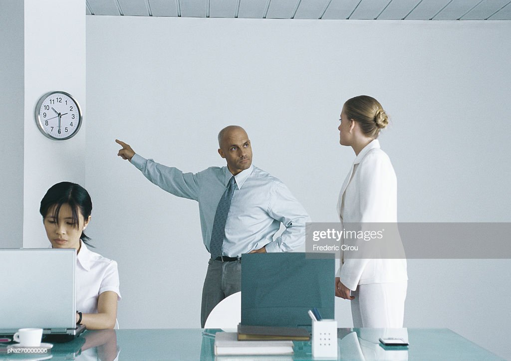 In office, woman sitting working at laptop, behind her man looking at second woman and pointing at clock : Stock Photo