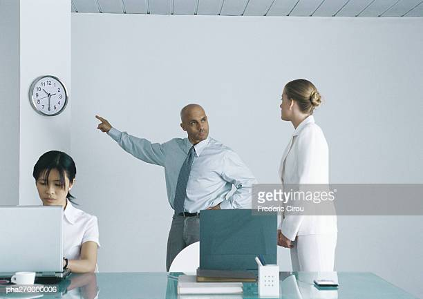 In office, woman sitting working at laptop, behind her man looking at second woman and pointing at clock