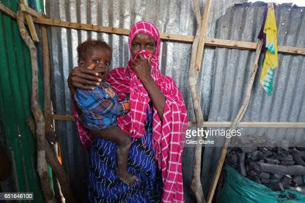 In one of the many Internally Displaced Person's camp in and around Mogadishu a Somali mother and child await humanitarian assistance in a crude and...