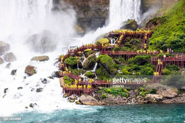 in ontario, on the canadian side, tourists all wearing yellow raincoats, are standing next to the beautiful horseshoe falls, part of the famous niagara falls. - niagara river stock pictures, royalty-free photos & images