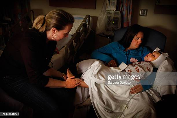 In pain and disorientated Staci Jami try to comfort Arefa shortly after her skin graft surgery at Shriner's Hospital for Children When Arefa first...