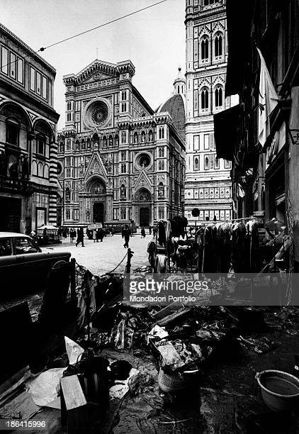 In piazza del Duomo the shopkeepers collecting the goods destroyed during the flood of the Arno River The Basilica of Santa Maria del Fiore stands...