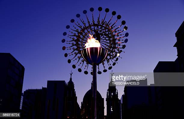TOPSHOT In picture the olympic flame during the Rio 2016 Olympic Games in front of the Candelaria church in Rio de Janeiro on August 13 2016 / AFP /...