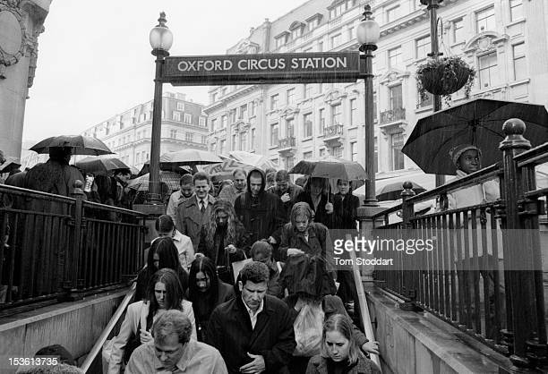In pouring rain city commuters crowd into Oxford Circus underground station in London's West End shopping district May 2001