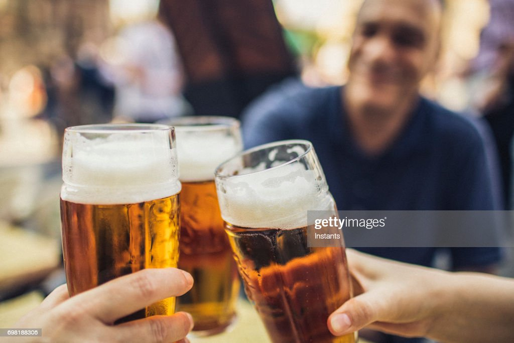 In Prague, three friends cheering on good news with glasses of pilsner beer. : Stock Photo