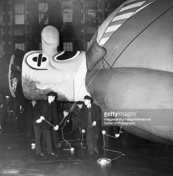 In preparation for the annual Macy's Thanksgiving Day parade balloon handlers hold the ropes of a clown filled with helium gas New York New York...