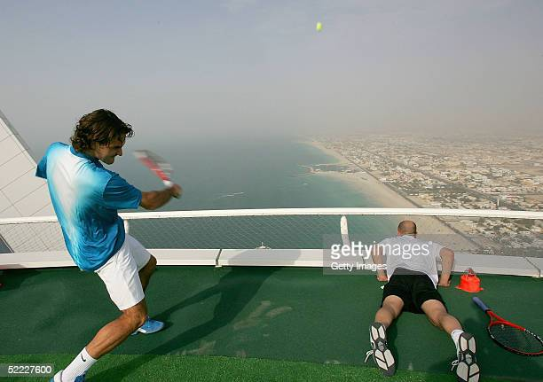 In preparation for the Dubai Duty Free Men's Open Roger Federer hits a tennis ball from the world's most unique tennis court the Helipad of the Burj...