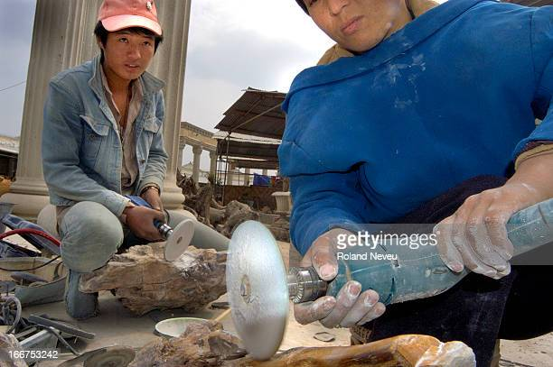 In Ruilli near the Chinese border with Burma, migrant Burmese worker polishing fossilised wood imported from Burma..