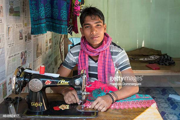 In Ruma village, upstream from Bandarban on the Sangu River, a young man is sewing inside his shop.