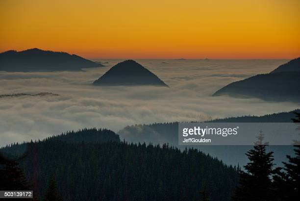 Montagne sopra la nebbia al tramonto