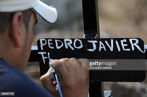 In Spanish by Noe Leiva A nephew of Honduran builder Pedro Funez, helps him paint the crosses over the grave of his children at the cemetery for the...