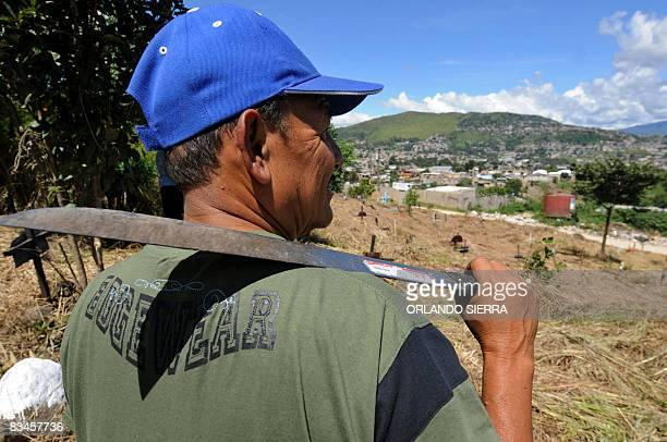 STORY in Spanish by Noe Leiva Honduran builder Pedro Funez holds the machete he used to clear the grass grown over the graves of his family at the...
