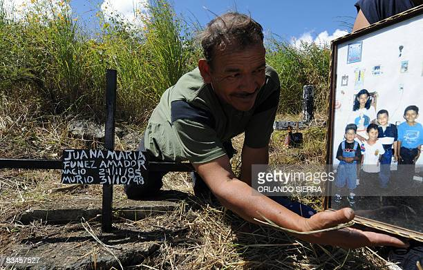 In Spanish by Noe Leiva Honduran builder Pedro Funez, looks at a picture of his daughter Juana Maria, over her grave at the cemetery for the poor...