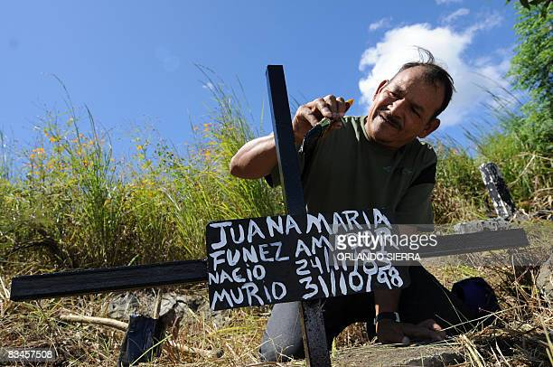 STORY in Spanish by Noe Leiva Honduran builder Pedro Funez paints the cross on the grave of his daughter Juana Maria at the cemetery for the poor...
