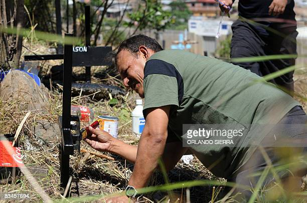 STORY in Spanish by Noe Leiva Honduran builder Pedro Funez paints the cross over the grave of one of his children at the cemetery for the poor Divino...