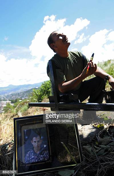STORY in Spanish by Noe Leiva Honduran builder Pedro Funez talks to God as he paints the cross over the grave of one of his children at the cemetery...