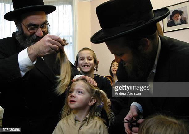 In Stamford Hill London United Kingdom on the 3rd birthday of a Orthodox Jewish boy he has his first ever hair cut leaving his peyos to grow Here his...
