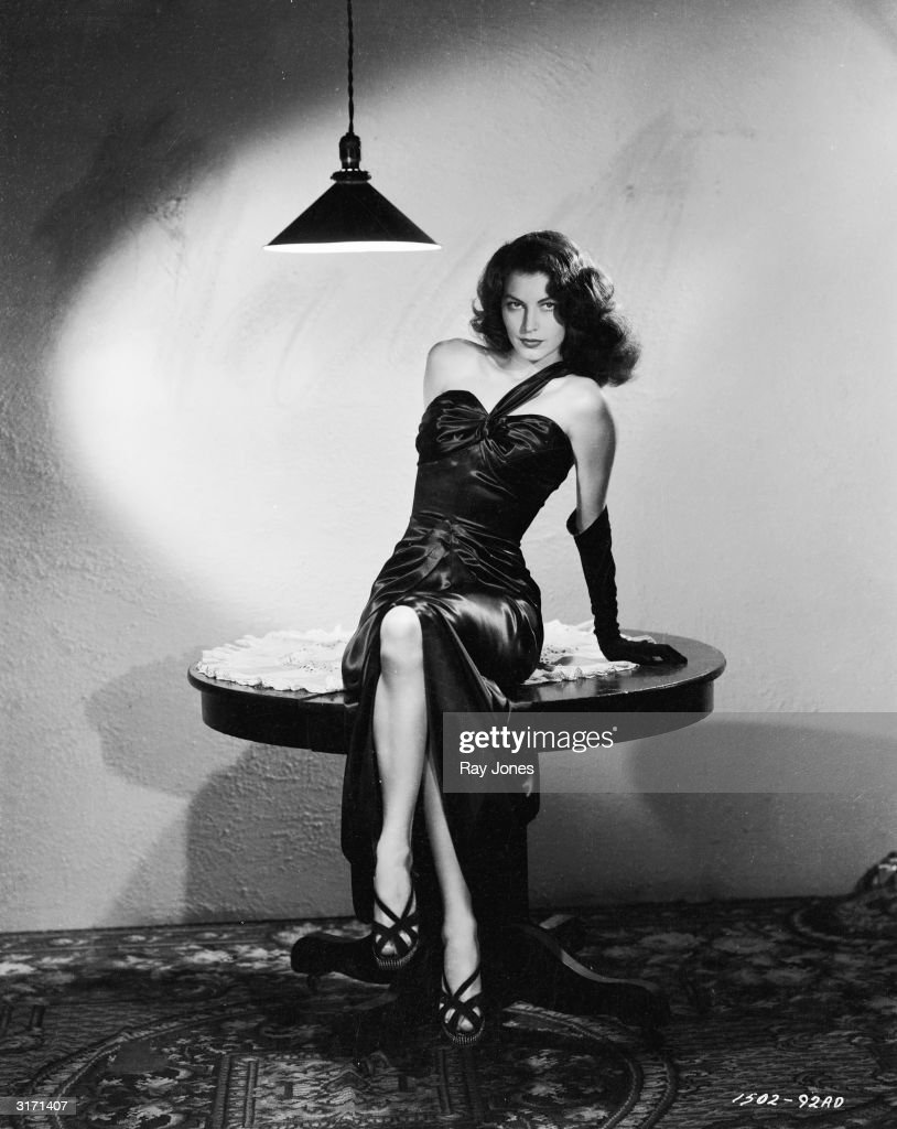 In stark surroundings American actress Ava Gardner poses in a sleek black satin dress in a scene from Robert Siodmak's film noir, 'The Killers'.
