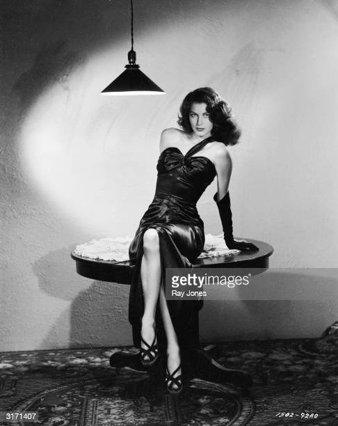 In stark surroundings American actress Ava Gardner poses in a sleek black satin dress in a scene from Robert Siodmak's film noir 'The Killers'