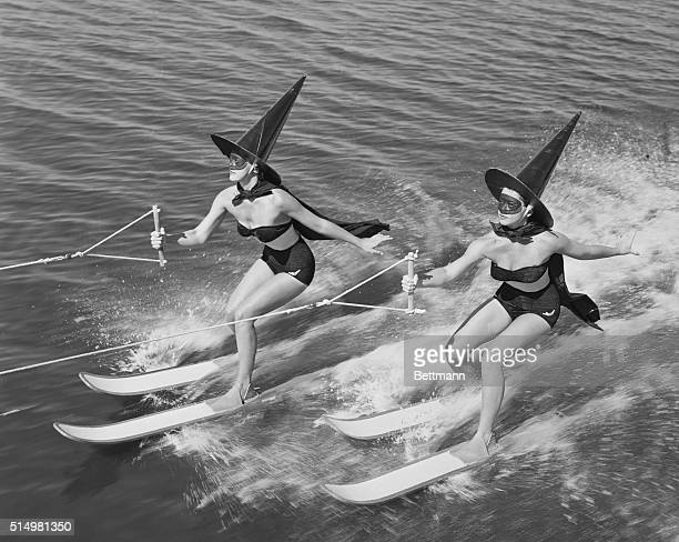 In suitable witches raiment two sorcerers of Cypress Gardens switch from broomsticks to broomskiis to herald the dawn of Halloween