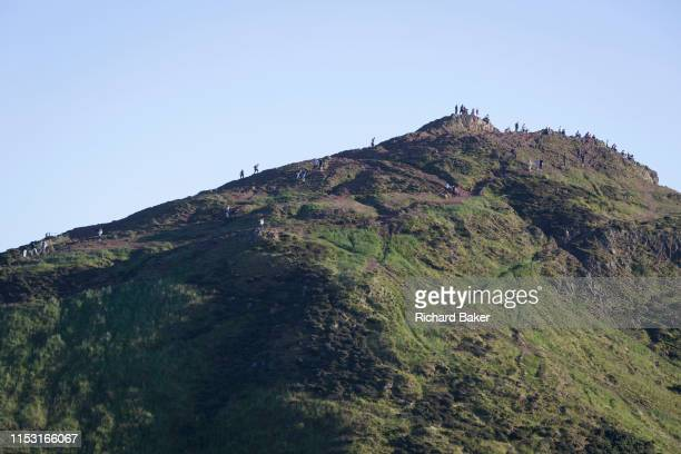 In summer evening sunshine walkers climb the last metres to the summit of Arthur's Seat in Holyrood Park that overlooks the city of Edinburgh on 26th...