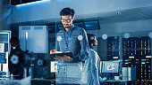 In Technology Research Facility: Chief Engineer Stands in the Middle of the Lab and Uses Tablet Computer. Team of Industrial Engineers, Developers Work on Engine Design Use Digital Whiteboard and Computers