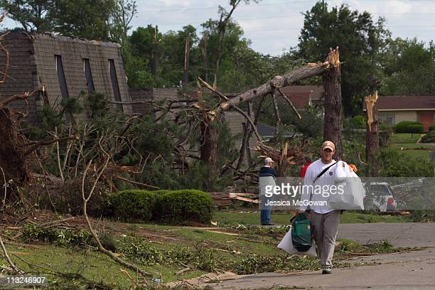 In the aftermath of a severe tornado, University of Alabama senior Bradley Dorsett carries his belongings from his damaged apartment on April 28,...
