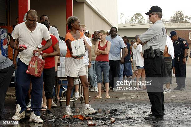In the aftermath of Hurricane Katrina two people carry food and drinks collected at a grocery store as a police officer watches 31 August in Biloxi...
