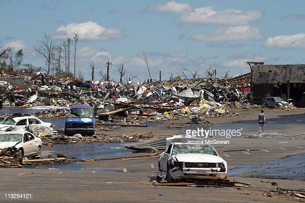 In the aftermath of Wednesday night's storms, a few people traverse through the damage and destroyed cars in a shopping center on McFarland Blvd. On...
