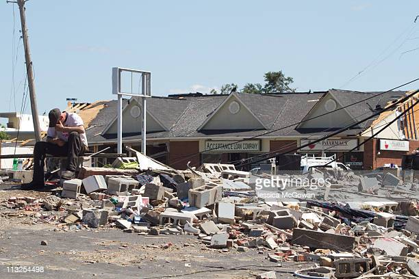 In the aftermath of Wednesday night's storms, an employee of a demolished oil change shop hangs his head while resting on the pile of debris where...