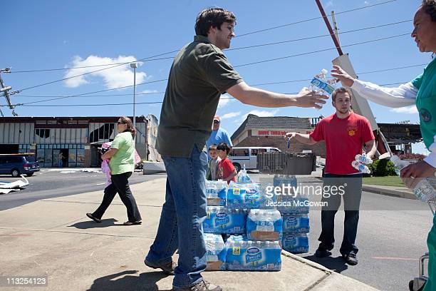 In the aftermath of Wednesday night's storms, CVS managers Ryan Storm and Cory Lewis hand out free water to residents in front of the damaged CVS on...