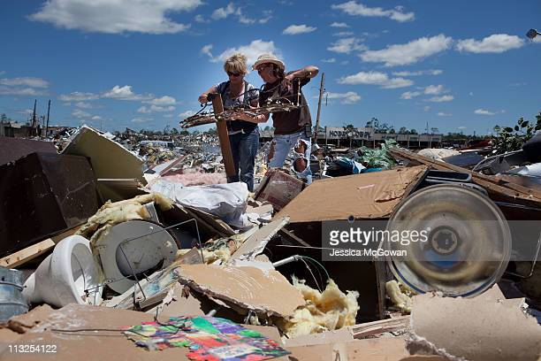 In the aftermath of Wednesday night's storms, Deron Hallman and salon owner Karen Barr try to salvage items from the leveled Hair Shack on April 28,...