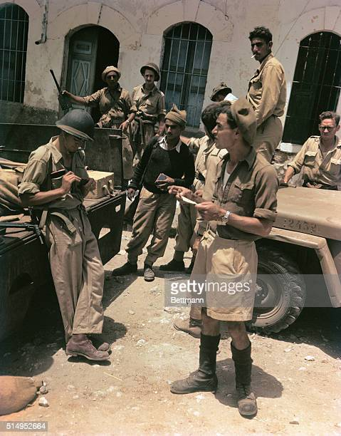 In the Arab village of Kakoun Haganah troops stand near military vehicles One soldier examines Arab knife taken as a souvenir