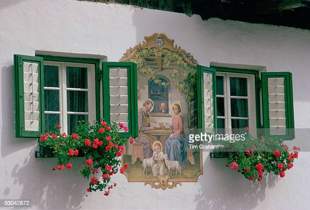 In the Austrian Tyrol a farmhouse mural depicting baby Jesus with a halo hugging lambs with his parents Mary and Joseph nearby This religious mural...