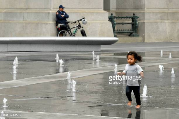 In the background a police officer keeps a watchful eye as children play in the fountain at Dilworth Park in Philadelphia PA on September 11 2018