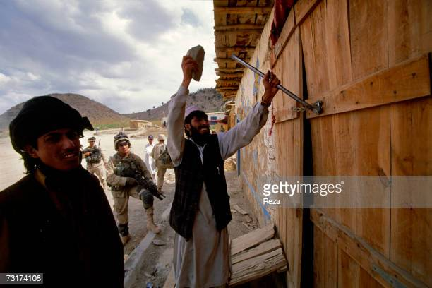 In the Bazaar of the village in the Pashtun tribal zone of Waziristan this Pashtun forces the lock of his shop in order to open the door to the...