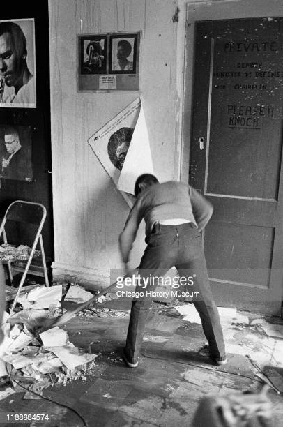 In the Black Panther Party's Illinois chapter headquarters , an unidentified man sweeps up after a police raid, Chicago, Illinois, July 31, 1969.