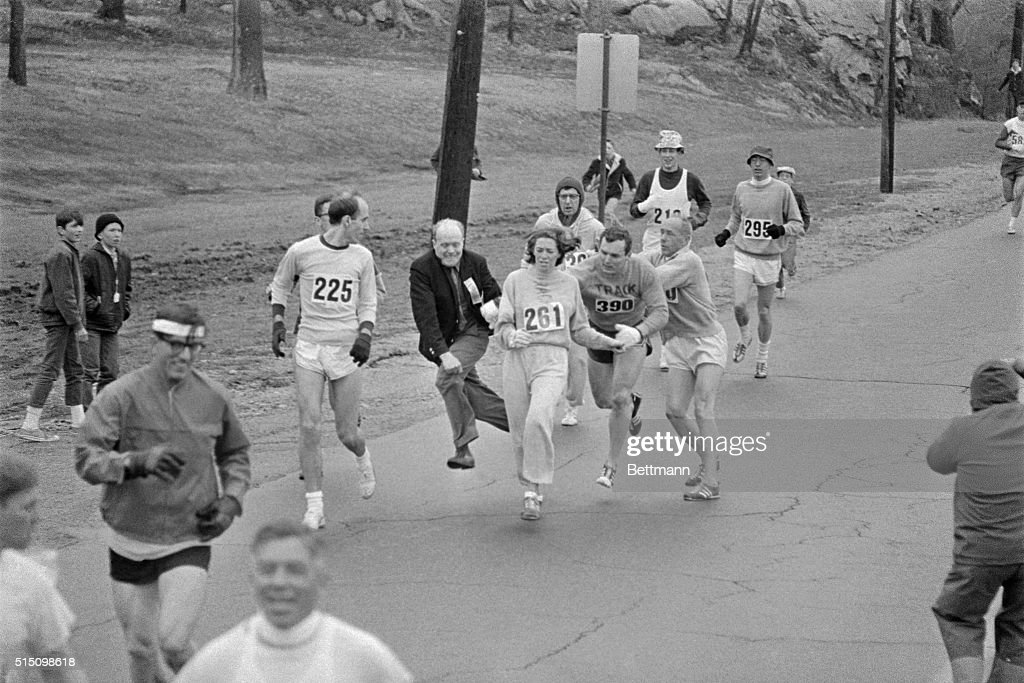 In the Boston Marathon, one of two women running in the normally all-male-race, Kathy Switzer, (261) of Syracuse, New York, is being hassled by BAA Marathon Director Bill Cloney, as he attempted to stop her from competing. The dark-haired girl did not show up for the physical examination required of all starters, (had she appeared at the starting line, she would never have been allowed to compete). she remained in the race, but was never seen near the finish line.
