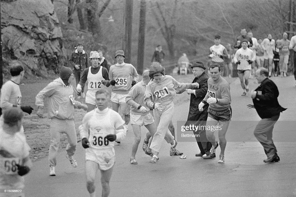 In the Boston Marathon, one of two women running in the normally all-male race, K. Switzer, (261) of Syracuse, New York, gets past Marathon Director Bill Cloney, (in dark suit) here, who attempted to stop her from running. The dark-haired girl did not show up for physical examination required of all starters, (had she appeared at the starting line, she would never have been allowed to compete). She remained in the race, but was never seen near the finish line.