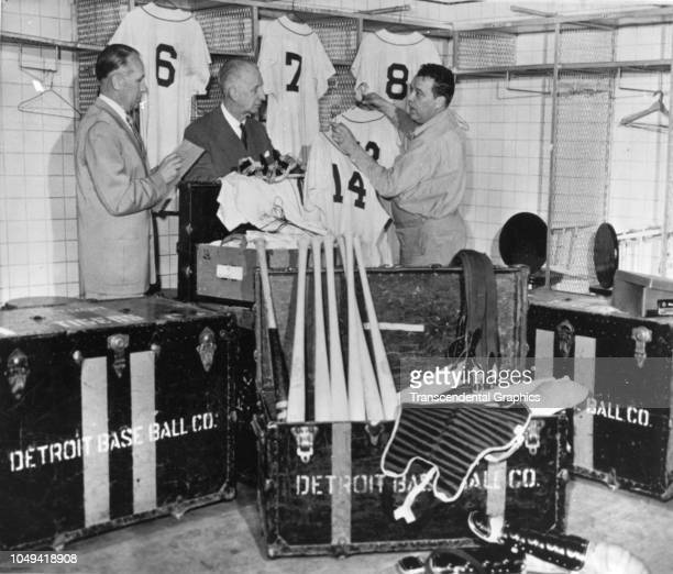 In the Briggs Stadium clubhouse unidentified equipment specialists for the Detroit Tigers pack team jerseys bats and other equipment into steamer...