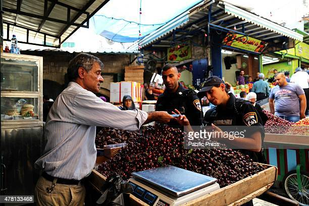 In the busy market of the Old City in Eastern Jerusalem a fruit vendor is asked for the identity card by Israeli policeOn the eve of Ramadan the holy...