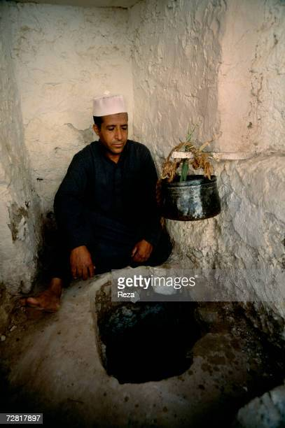 In the central square a man measures the water share for each garden through a pierced pot April 2000 in Ghadames Libya