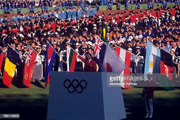 In the centre of the podium at the Olympic Stadium of Tokyo the gymnast Takashi Ono is raising his arm while he is pronouncing the Olympic Oath at...