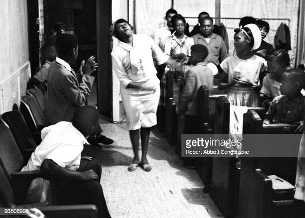 In the church aisle a woman sways as she is overcome with religious spirit during a service at the Temple Apostolic Church a storefront church in...